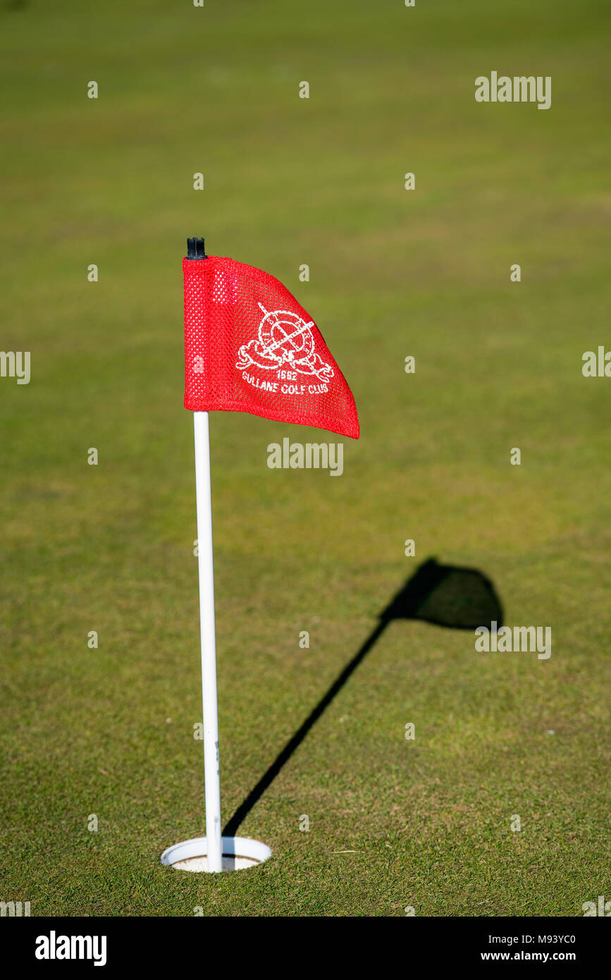 Detail of flag in hole of putting green at Gullane Golf Course in East Lothian , Scotland, United Kingdom - Stock Image