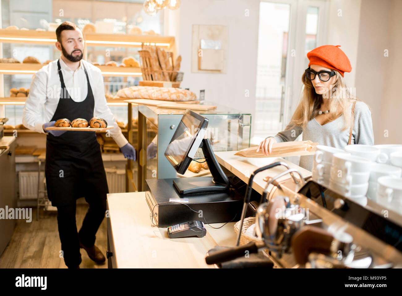 Seller with customer in the bakery store - Stock Image
