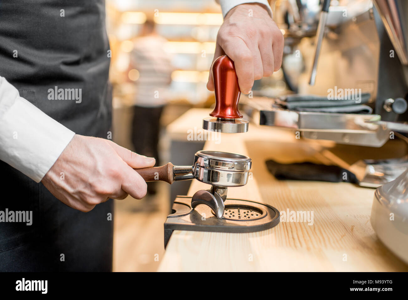 Pressing a coffee into the handle - Stock Image