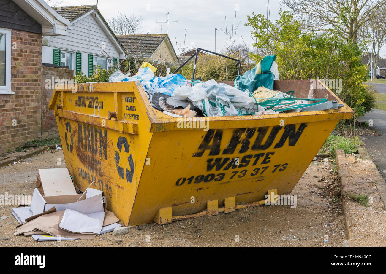 Building waste in a large metallic yellow skip in a driveway in the UK. - Stock Image
