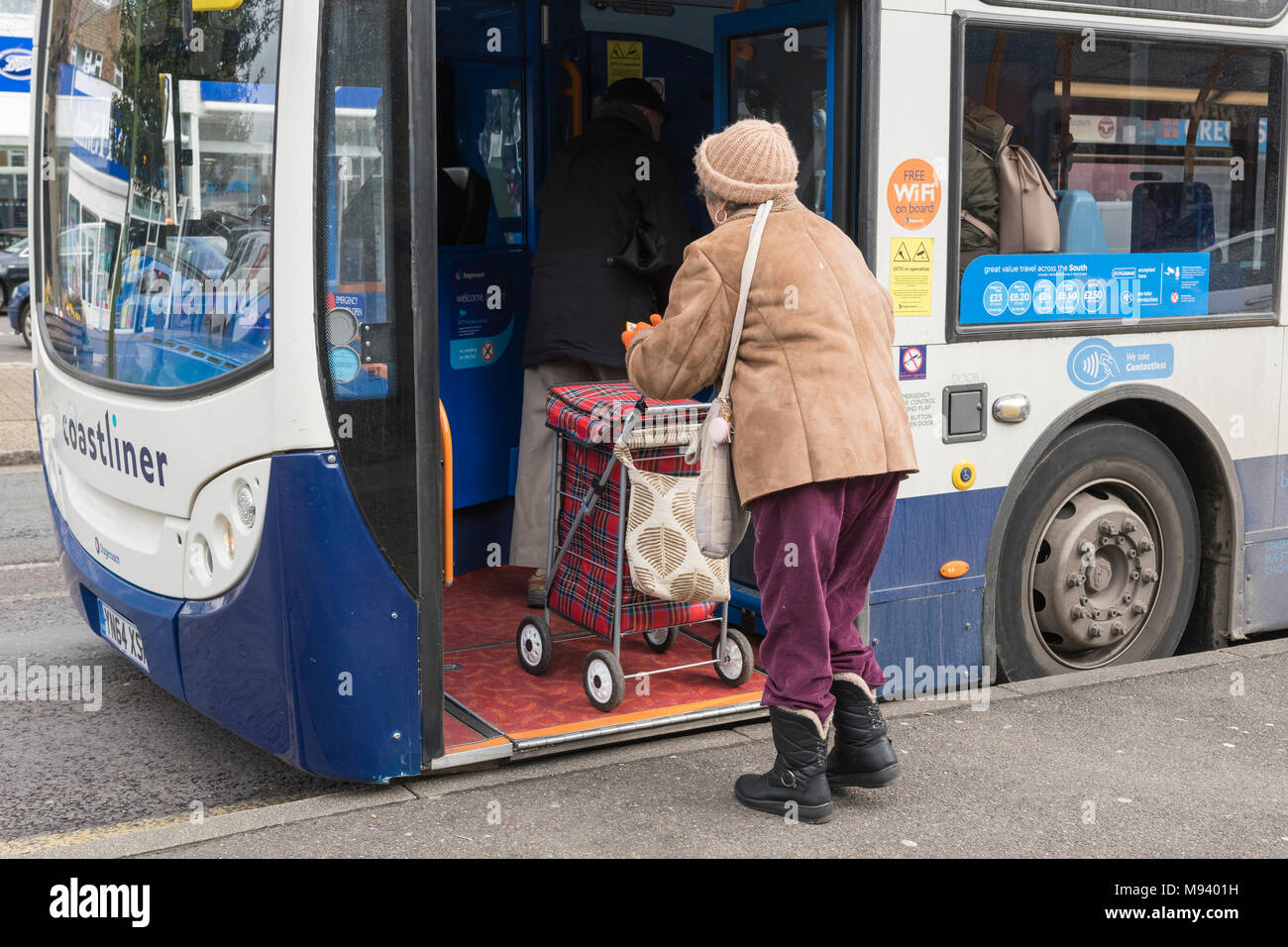 Senior woman boarding a bus with a wheeled shopping trolley in England, UK. - Stock Image