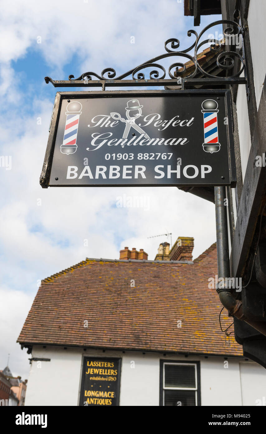Hanging barber shop sign at The Perfect Gentleman barbershop in Arundel, West Sussex, England, UK. Stock Photo