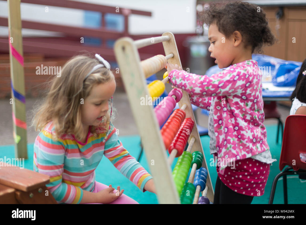 Two girls playing with an abacus at a nursery school in Warwickshire, UK Stock Photo