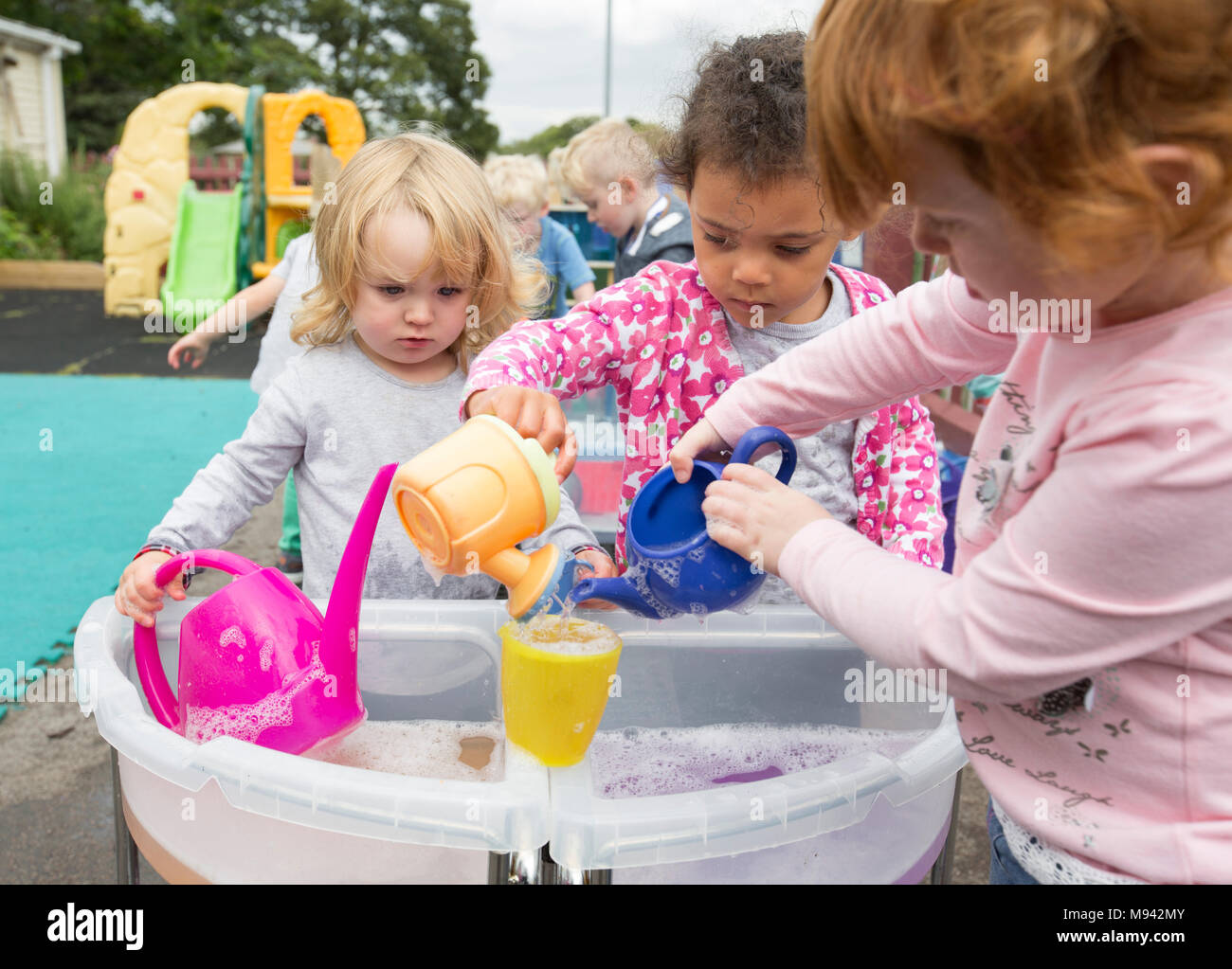 Nursery school children playing in a playground in Warwickshire, UK - Stock Image
