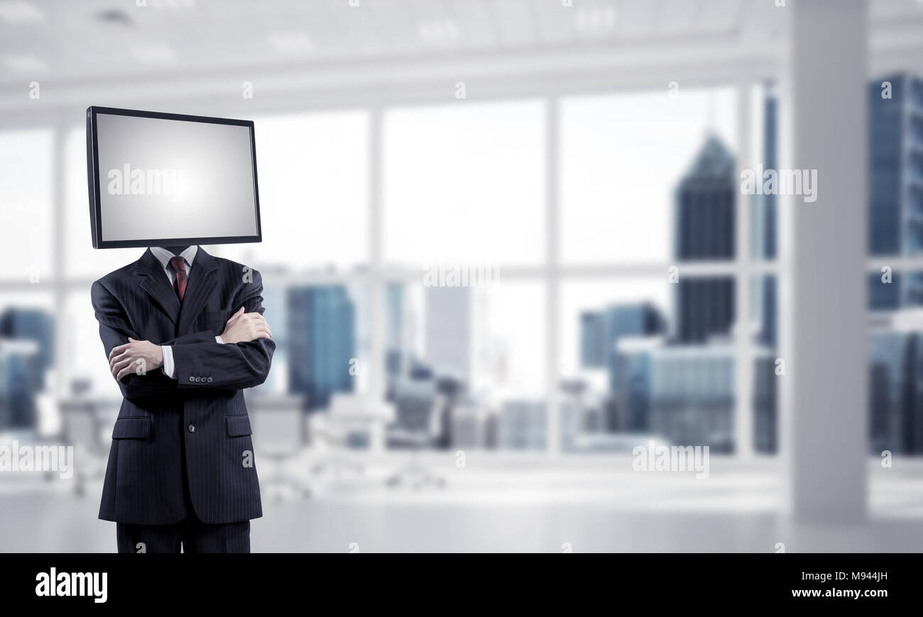 Cropped image of businessman in suit with TV instead of head keeping arms crossed while standing inside office building. Stock Photo