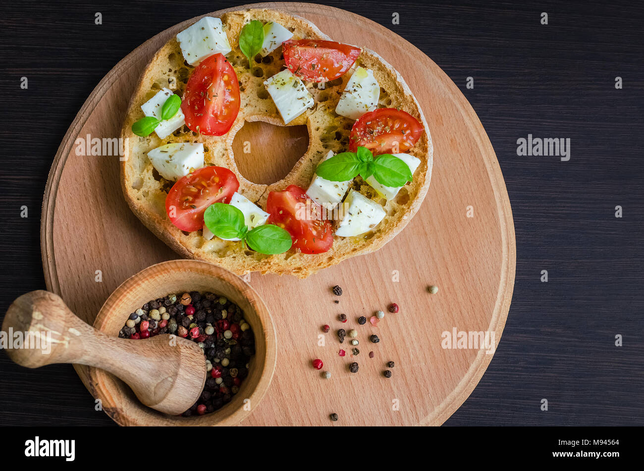 Classical frisella tomato, cheese mozzarella and basil. Italian starter friselle. Dried bread called freselle on wooden board. Italian food. Healthy v - Stock Image