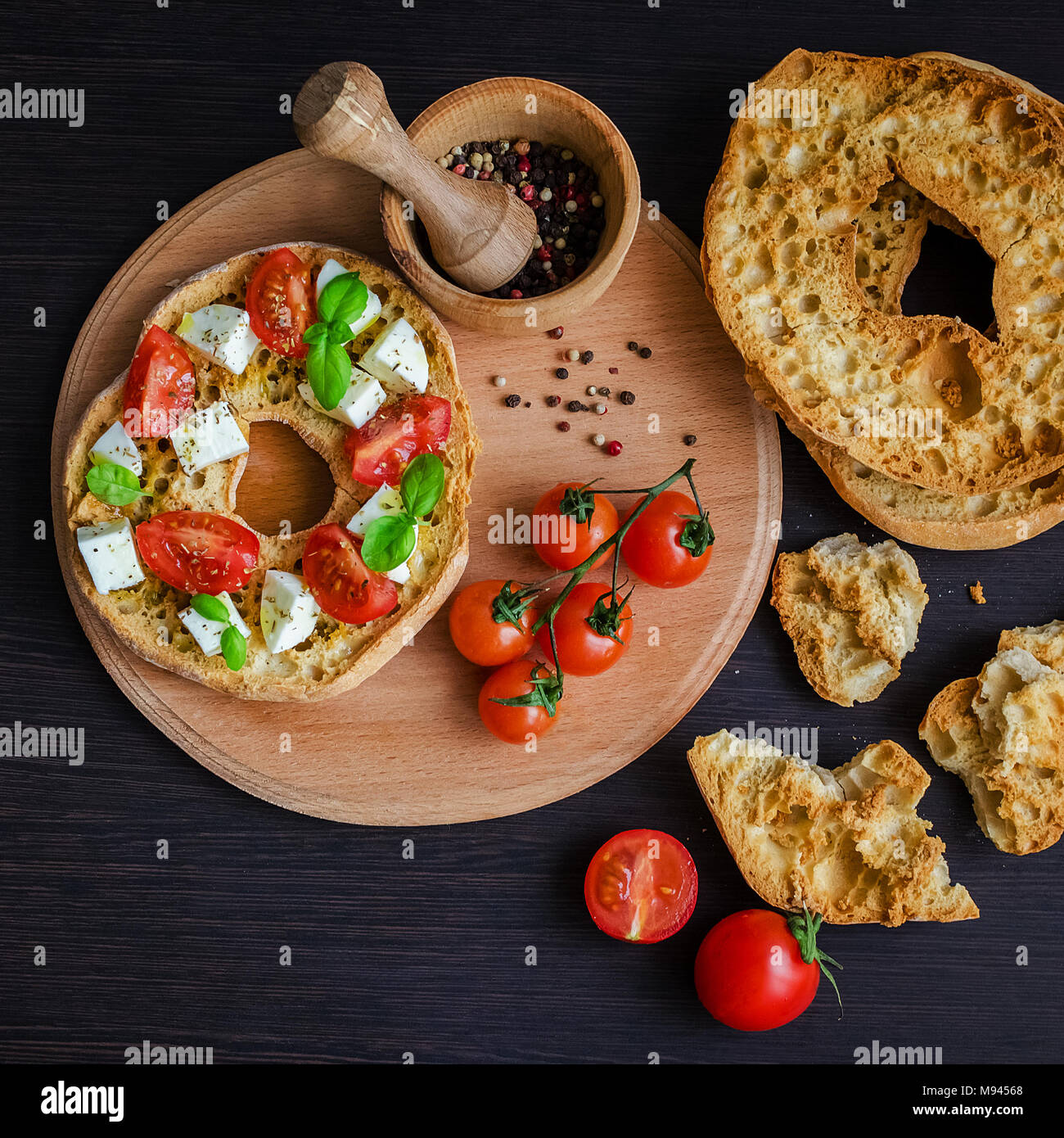 Italian appetizer Friselle. Italian dried bread Friselle on wooden board with tomatoes cherry, basil and peppercorns. Italian food. Healthy vegetarian - Stock Image