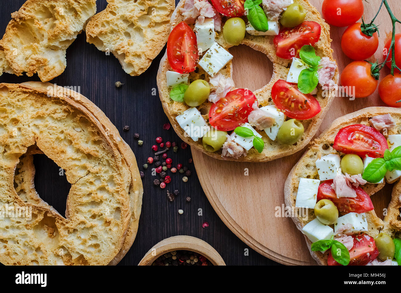 Italian appetizer Friselle. Italian dried bread Friselle on wooden board with tomatoes cherry, olives, tuna, basil and peppercorns. Italian food. Heal - Stock Image