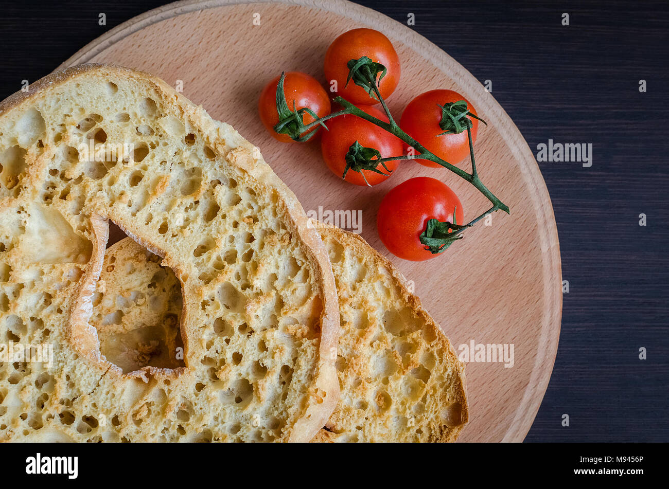 Italian dried bread Friselle on wooden board with tomatoes cherry. Italian food. Healthy vegetarian food. - Stock Image