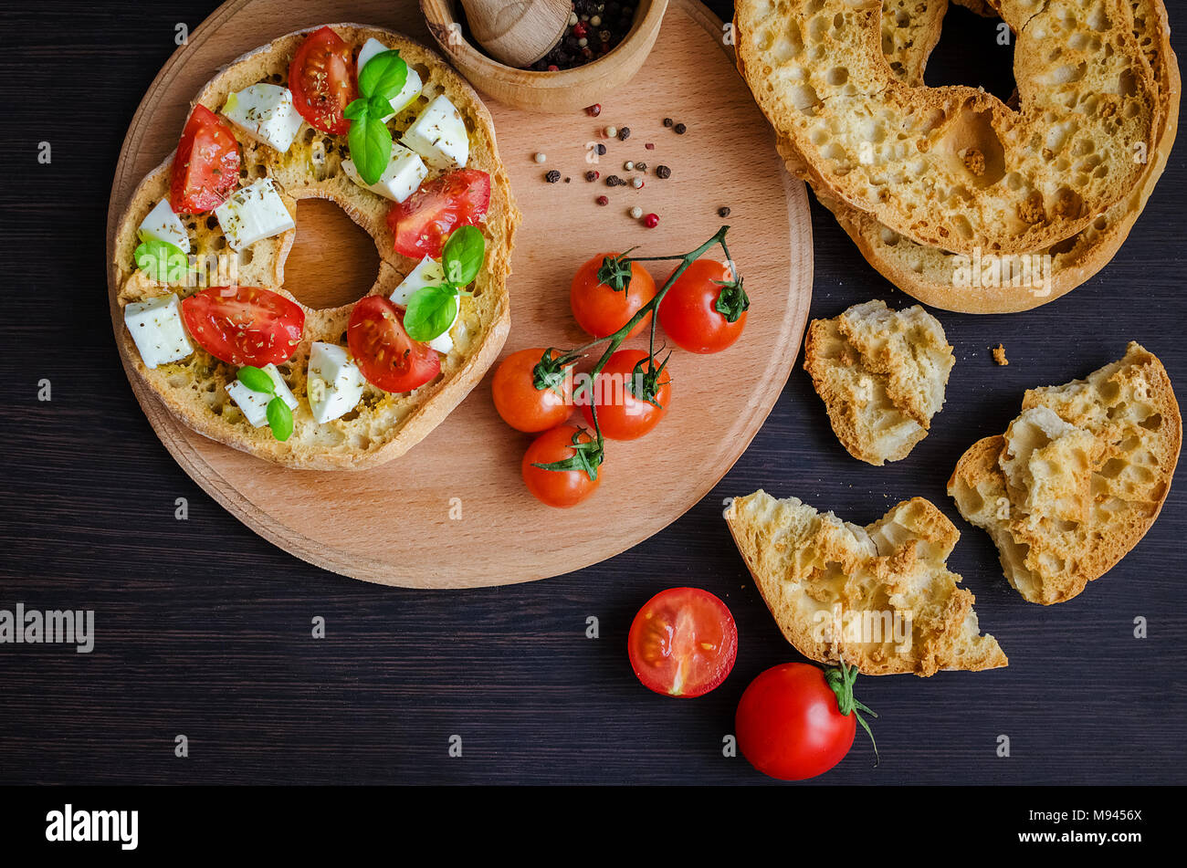 Italian appetizer Friselle. Italian dried bread Friselle on wooden board with tomatoes cherry, basil and pepper. Italian food. Healthy vegetarian food - Stock Image