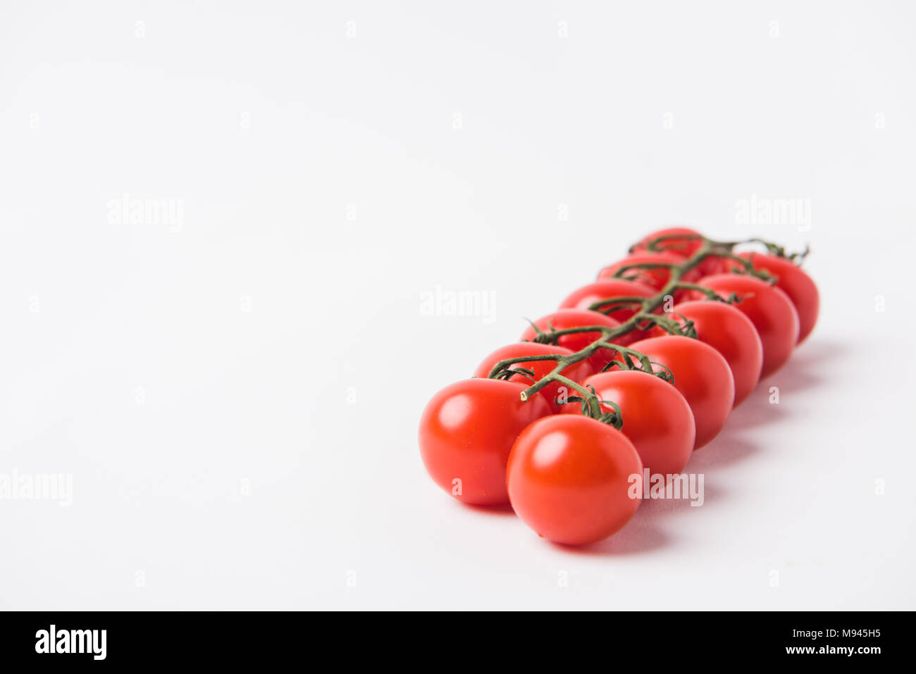 raw cherry tomatoes laying on white background Stock Photo