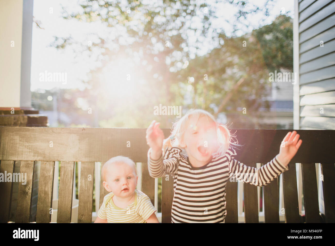 Girl and baby sitting on bench in sunshine Stock Photo