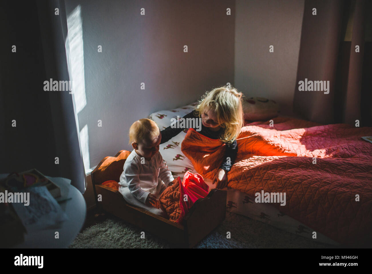 Girl and baby holding each other in separate beds - Stock Image