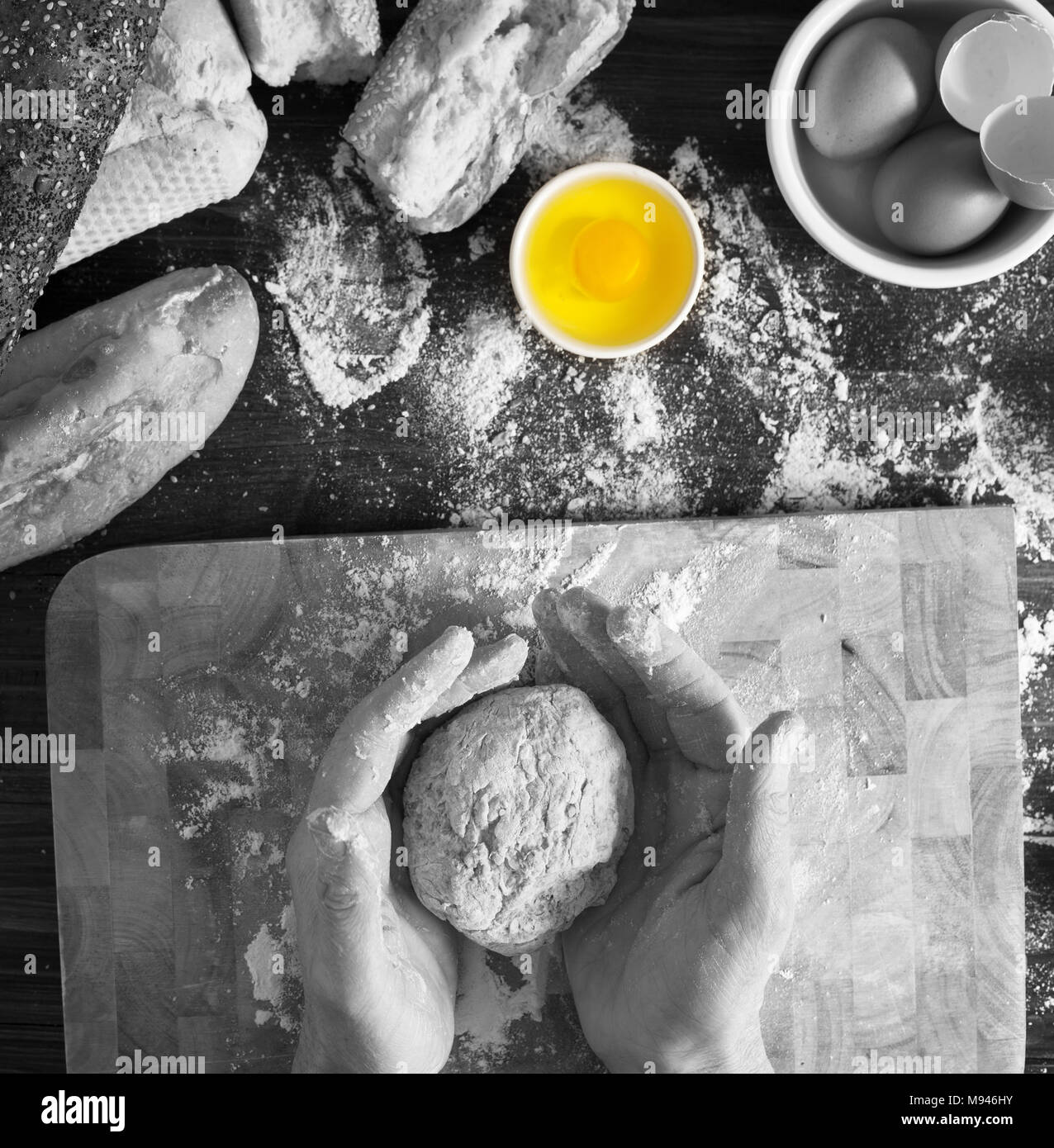 Black white shot with colour popping of egg image shows baker kneading organic dough