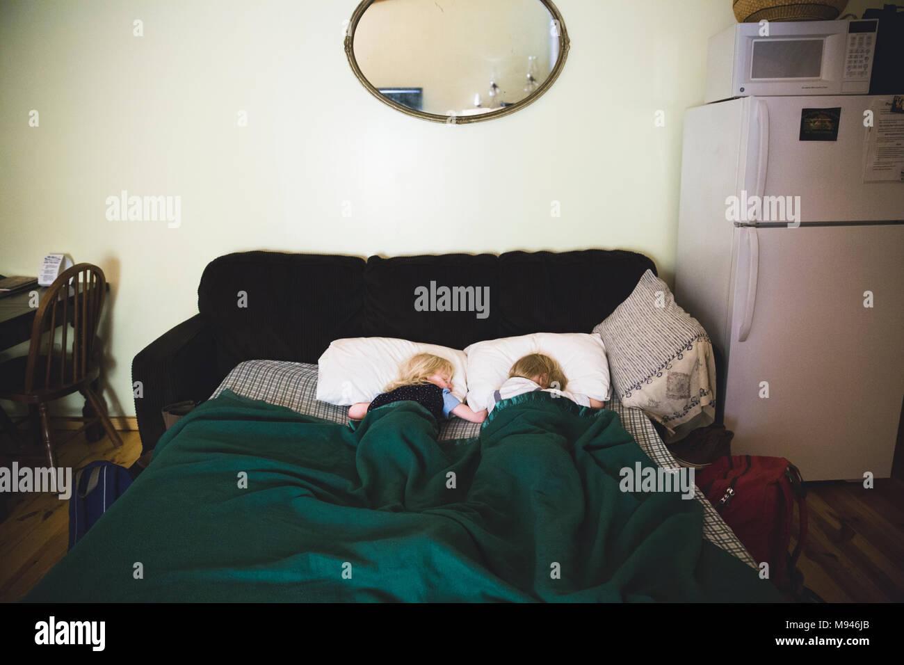 Children sleeping in sofa bed - Stock Image
