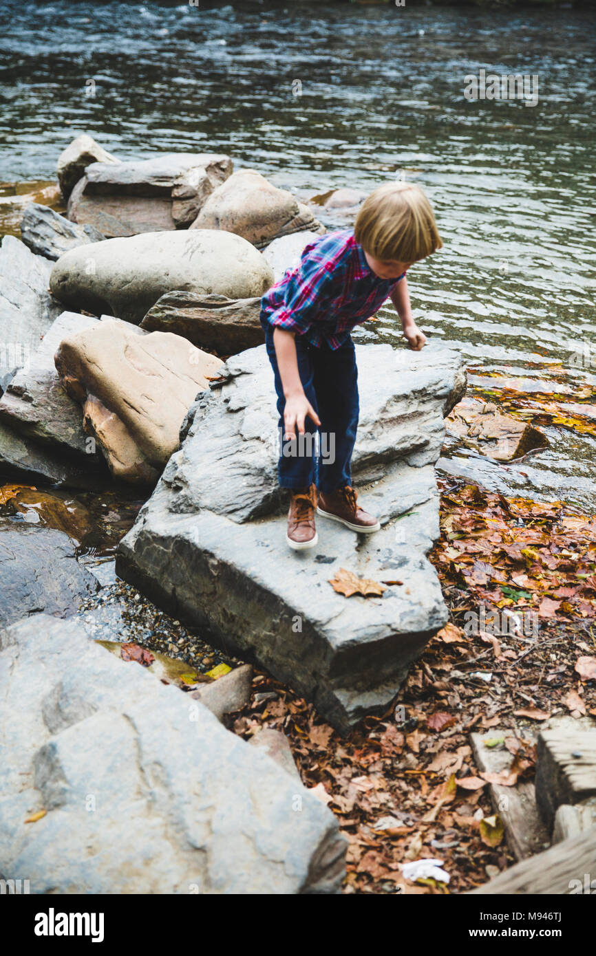 Boy playing on rocks next to river - Stock Image