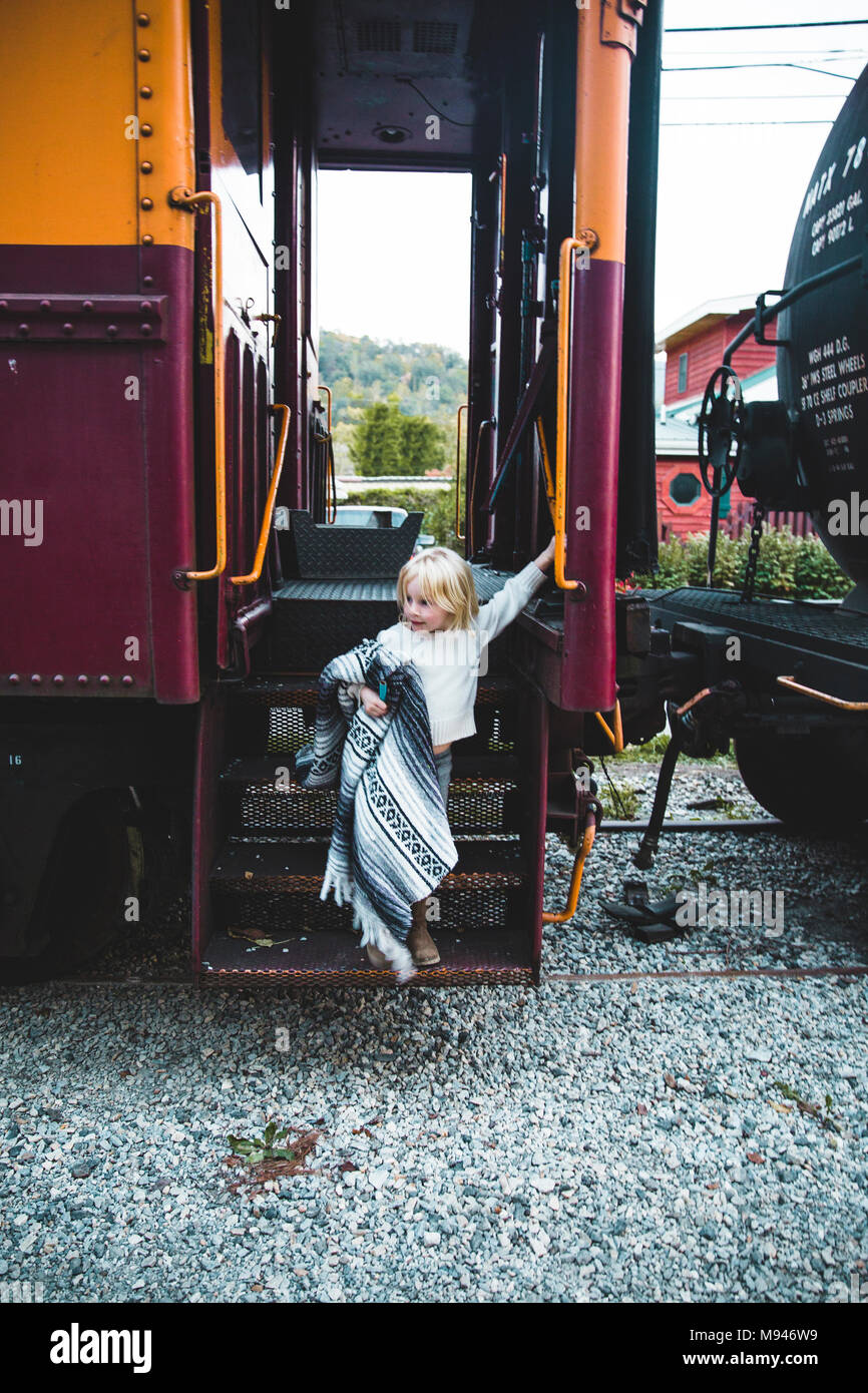 Girl with blanket coming out of train - Stock Image