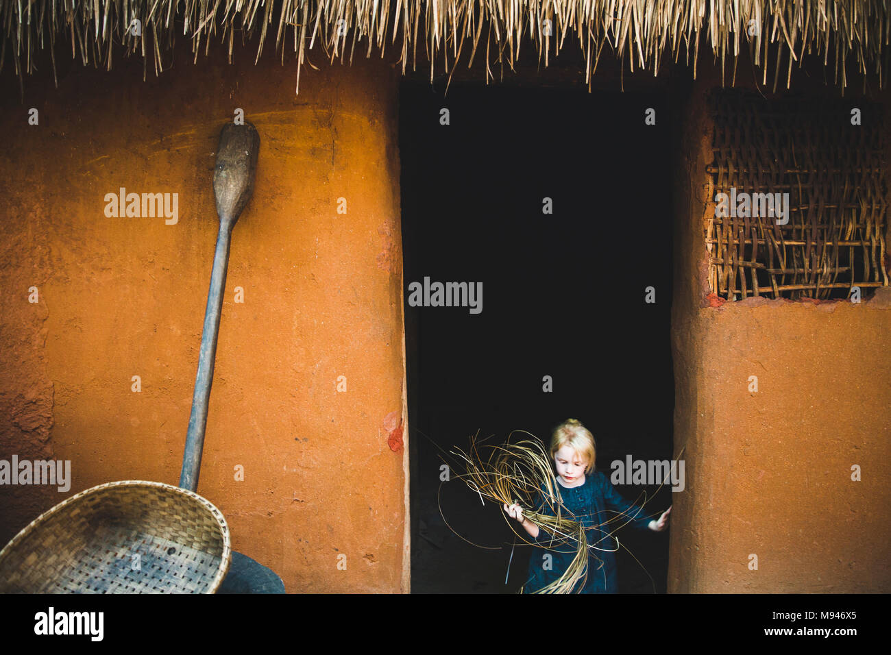 Girl carrying straw out of hut - Stock Image