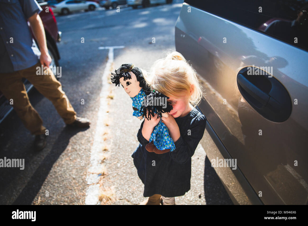 Girl hiding behind doll - Stock Image