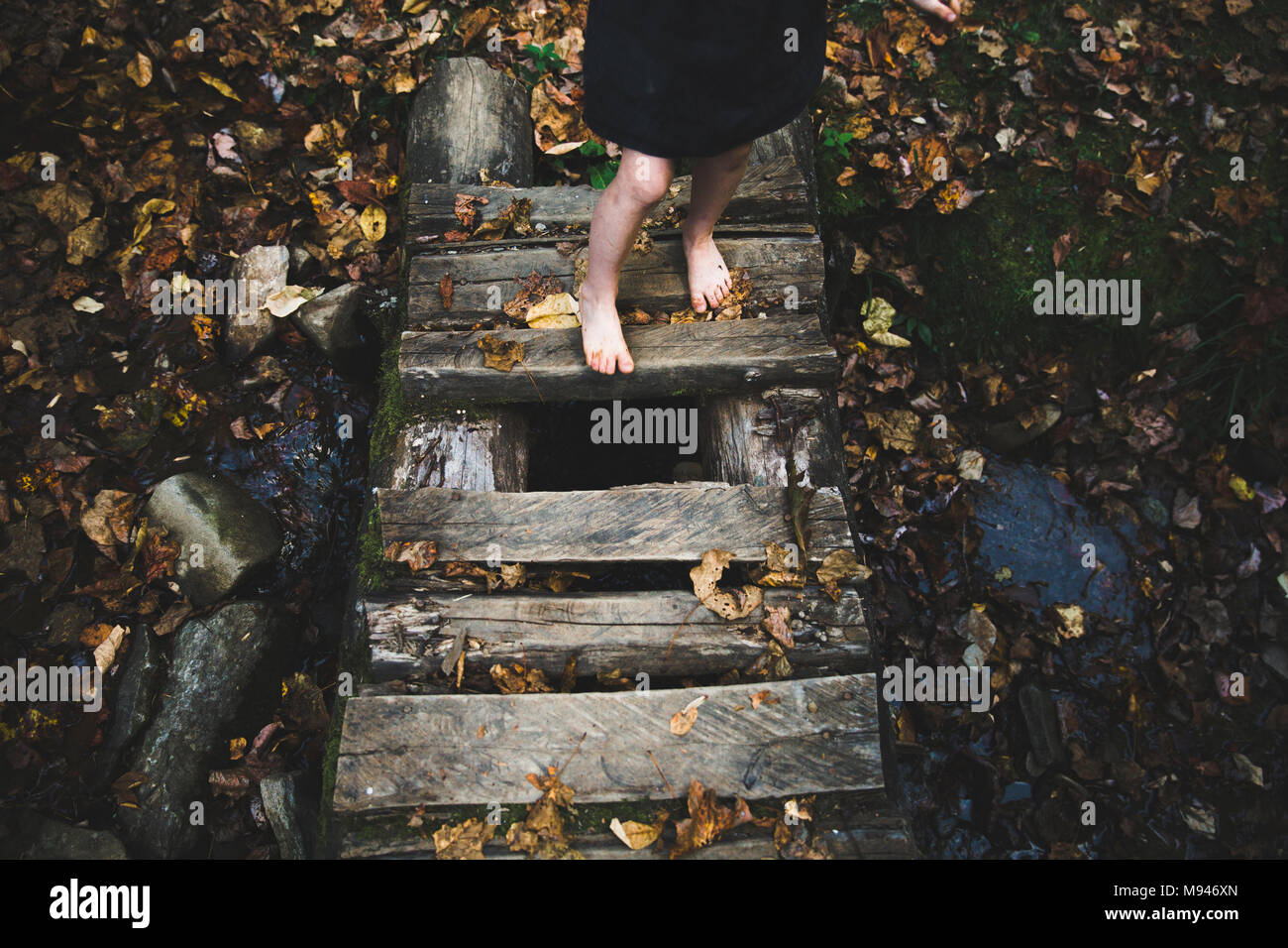Girl crossing small wooden bridge - Stock Image
