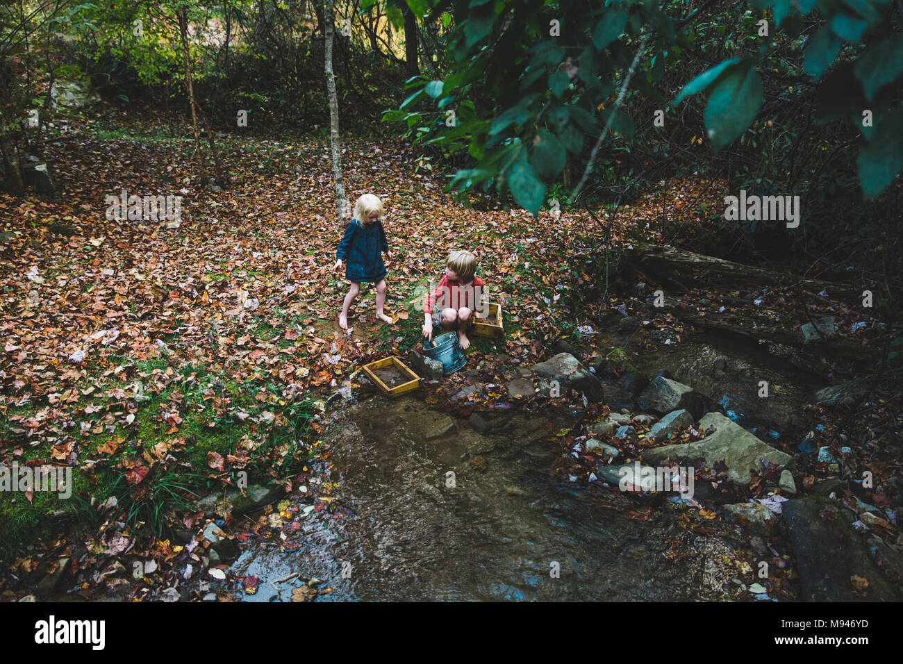 Children using panning buckets next to river - Stock Image