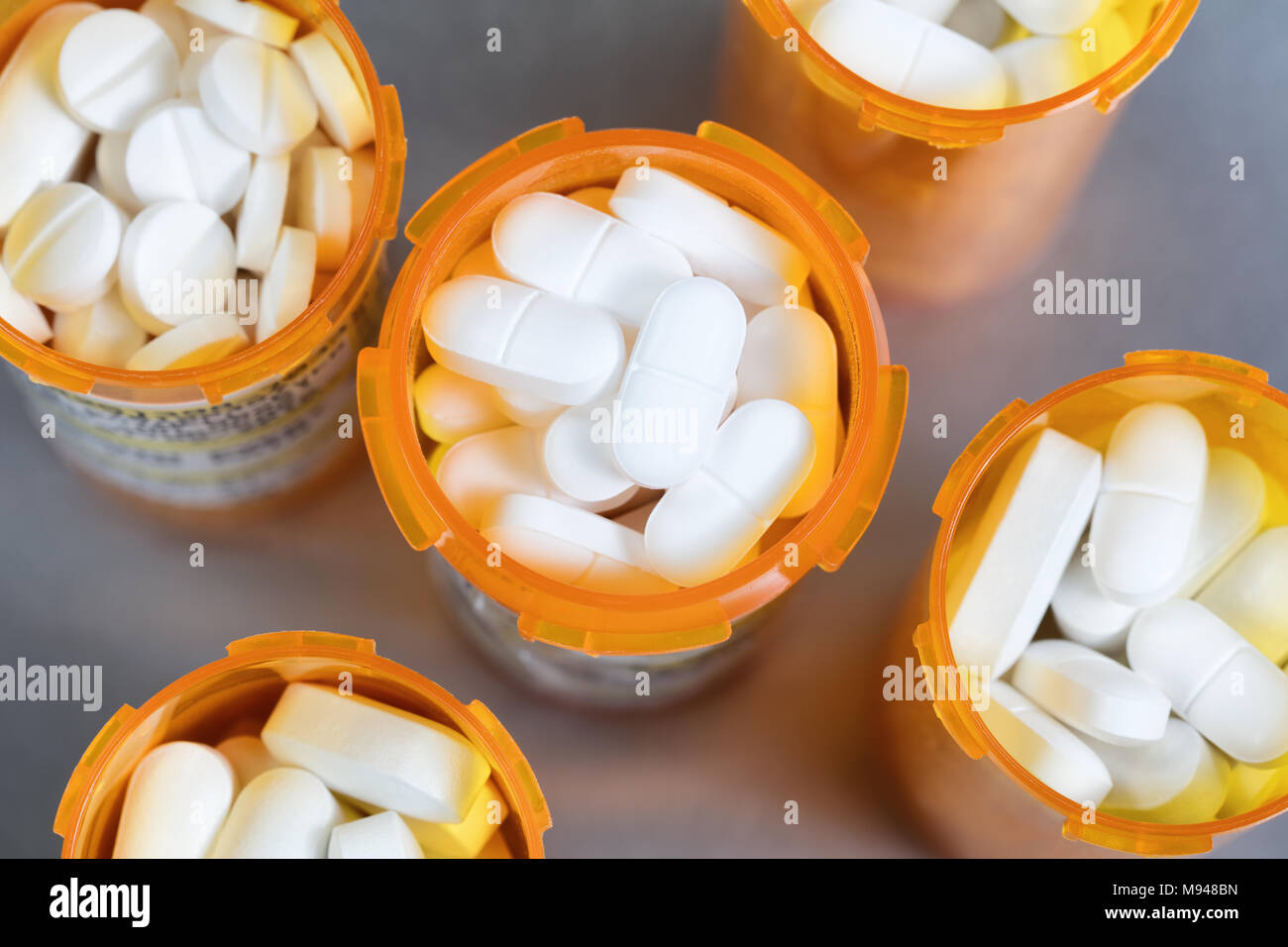 Close up overhead view of full prescription bottles on stainless steel background - Stock Image