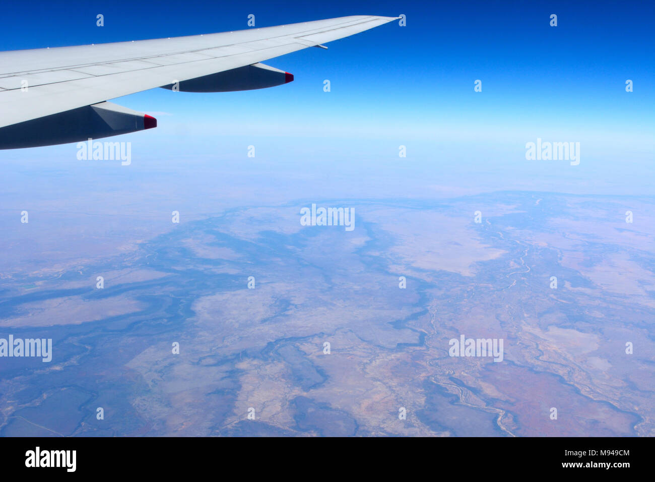 Wing of airplane flying over desert landscape in Australian outback. - Stock Image