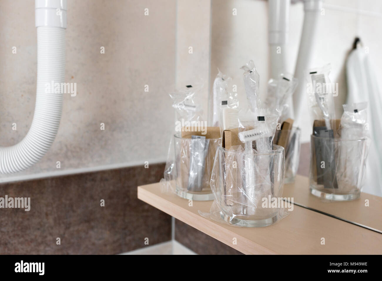Close up view on the bottles with cosmetics and hygienic kit ain the hotel bathroom - Stock Image