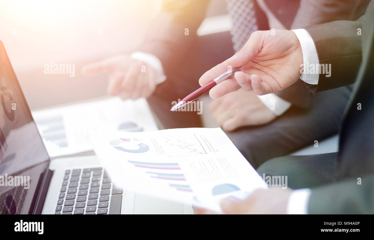 Business team hands at work with financial reports - Stock Image