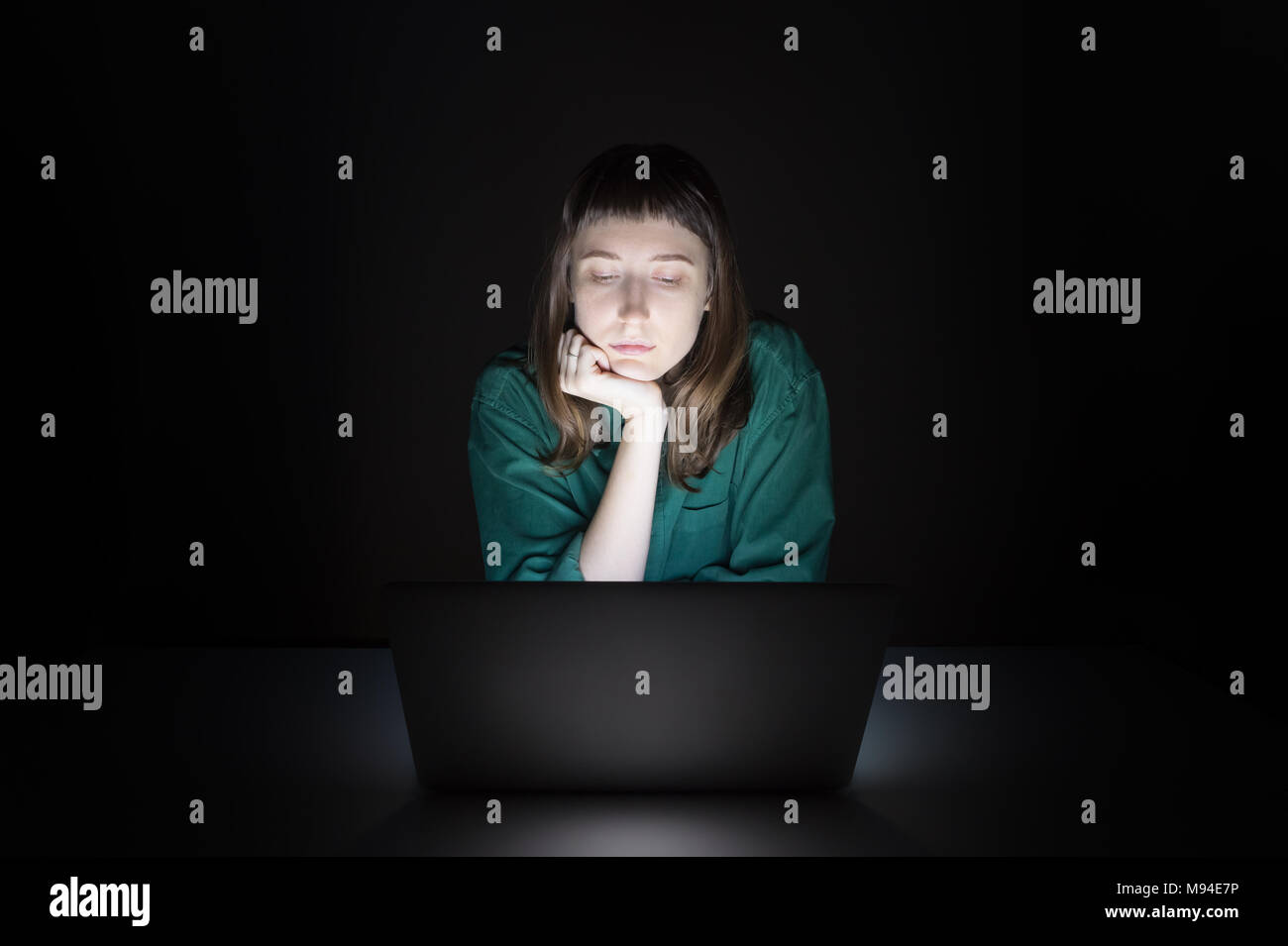 Woman at laptop computer indoors late in the evening. Portrait of young female student or worker sitting in front of computer screen at night and read - Stock Image