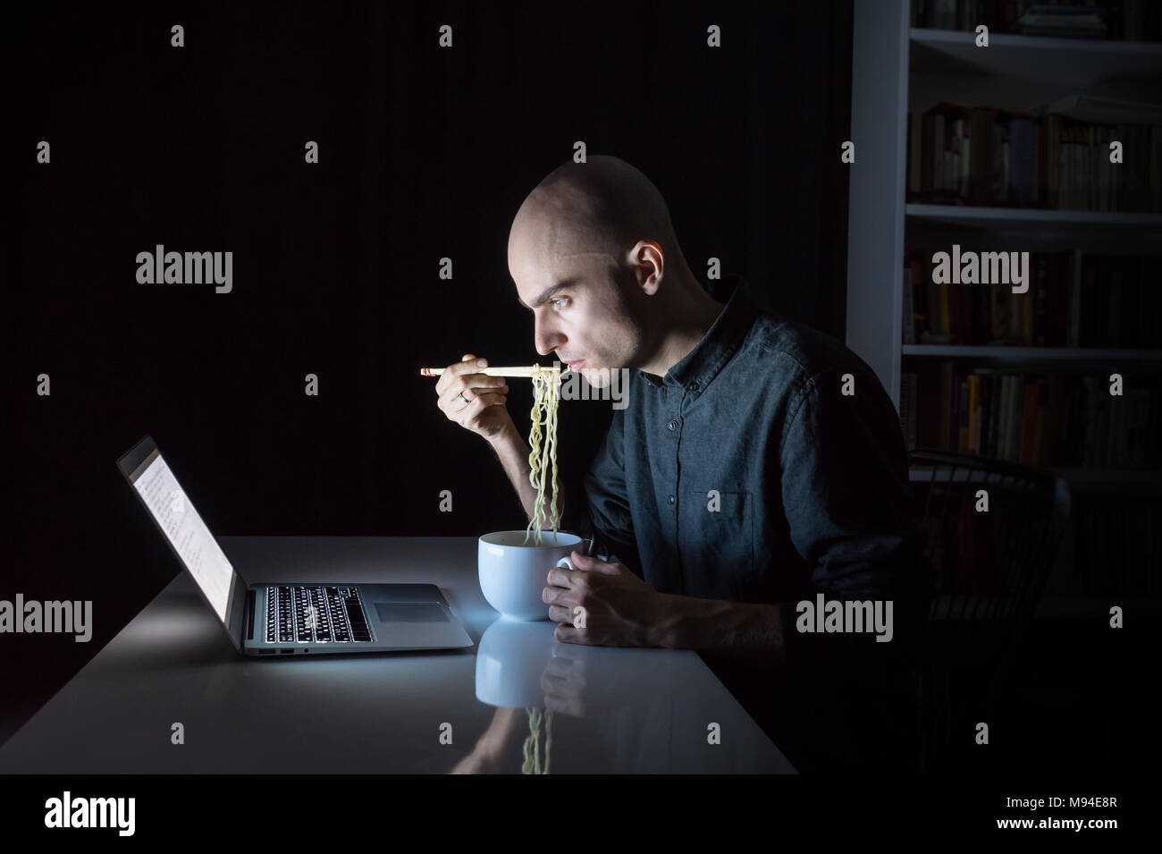 Young male at laptop computer eats instant ramen noodles with chopsticks late in the evening. Man working or studying online overtime at night has fas - Stock Image