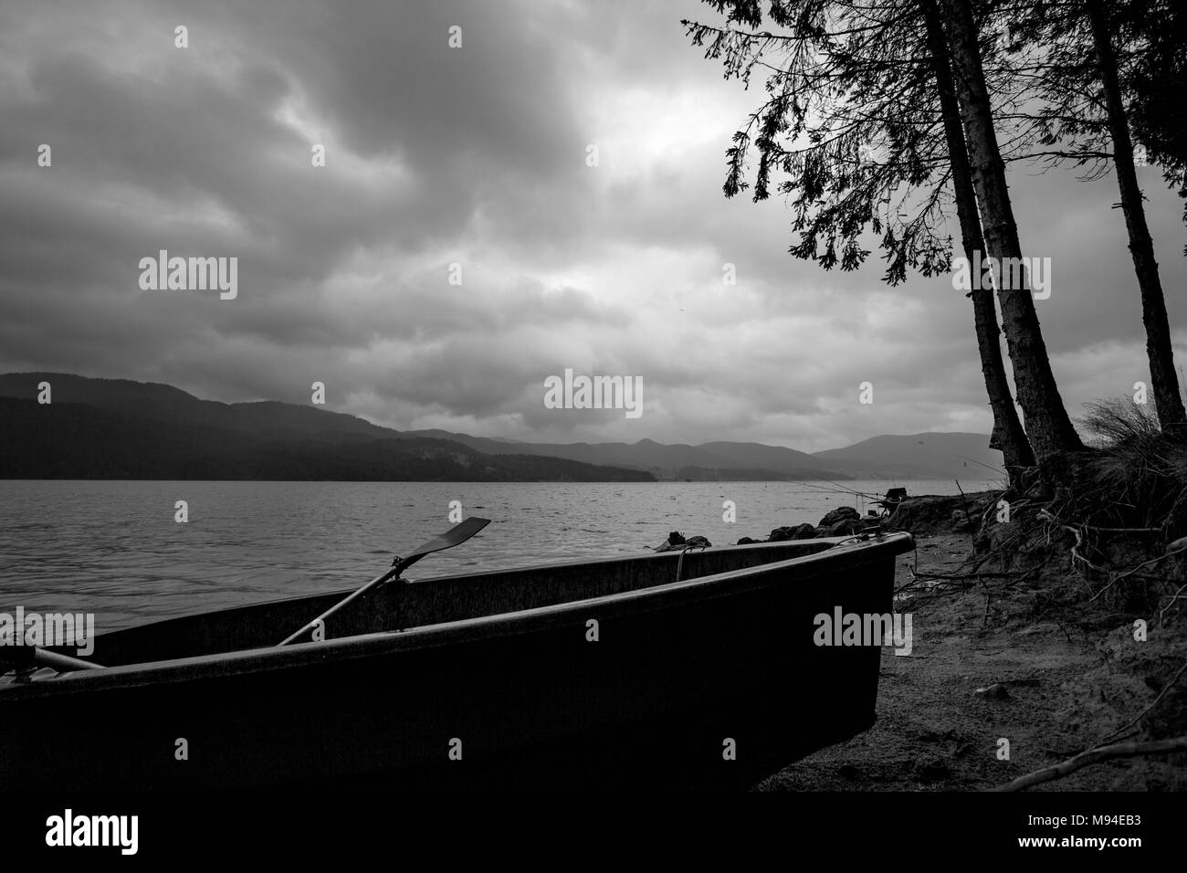 Small fishing boat silhouette at the shore with partial pines in cloudy dark rainy morning at lake Dospat, Rhodope mountain, Bulgaria Stock Photo