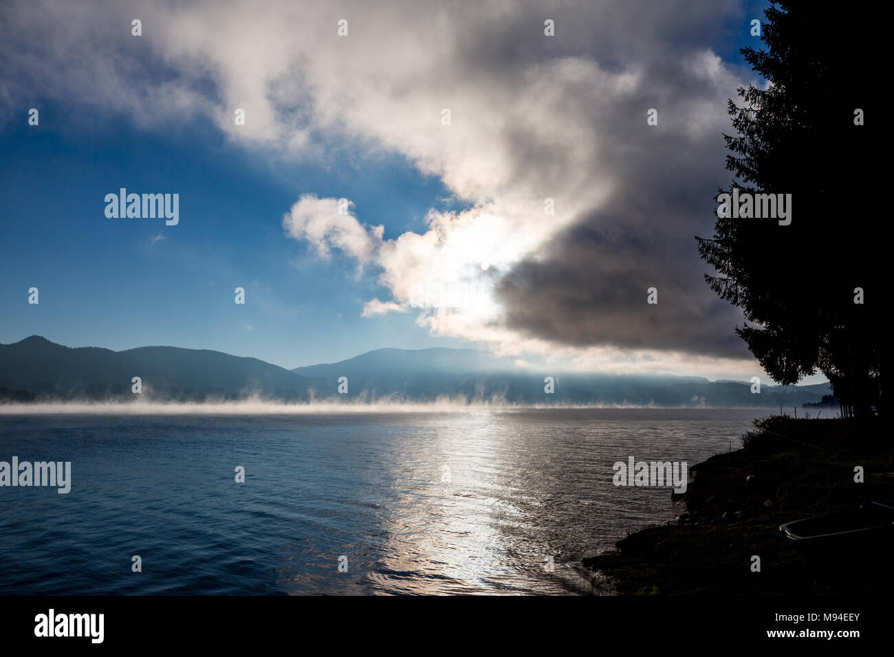 Autumn Sun coming out of clouds, light reflections on lake surface with water evaporations at lake Dospat, Rhodope mountains, Bulgaria - Stock Image