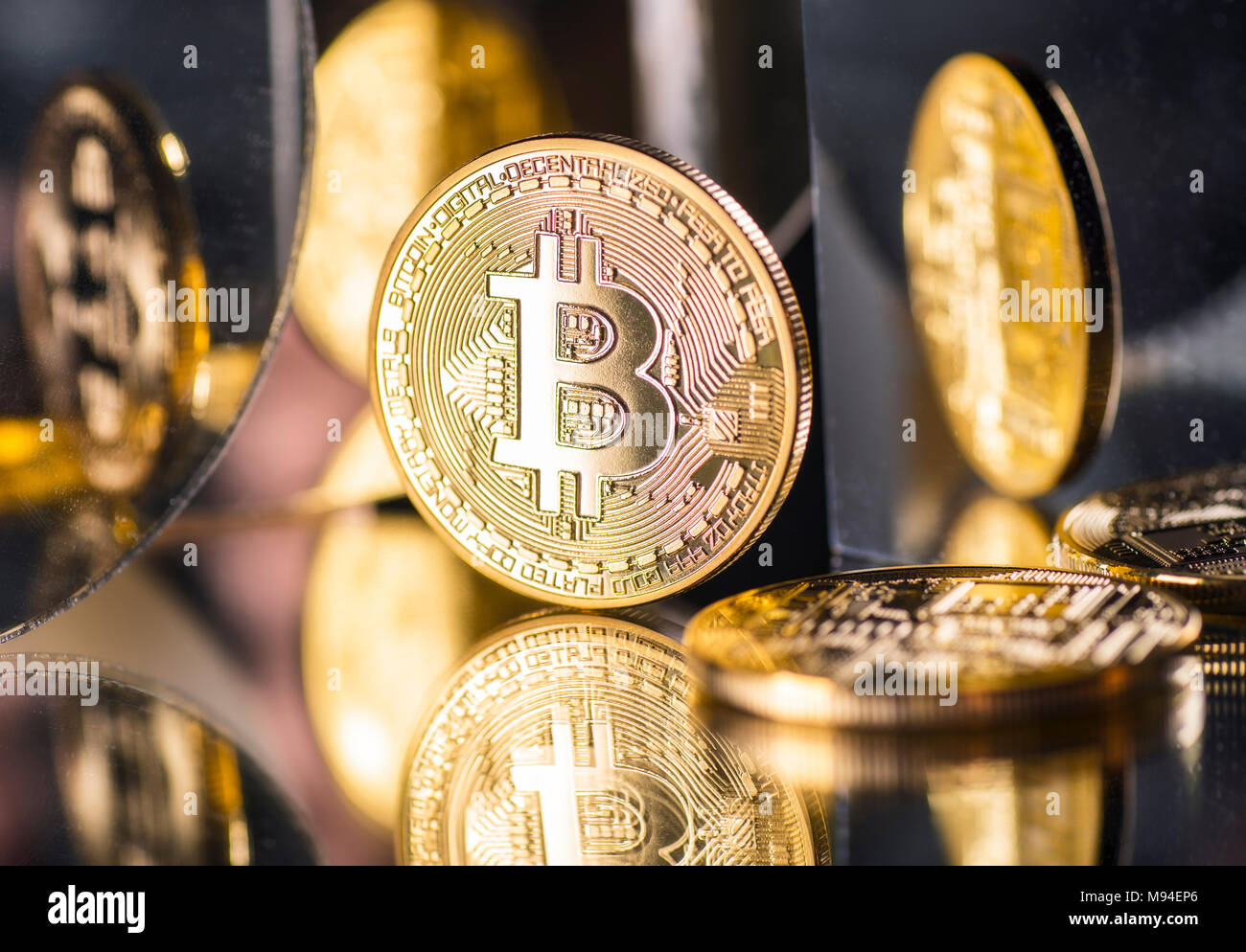 Coin of the crypto-currency Bitcoin with several reflections - Stock Image