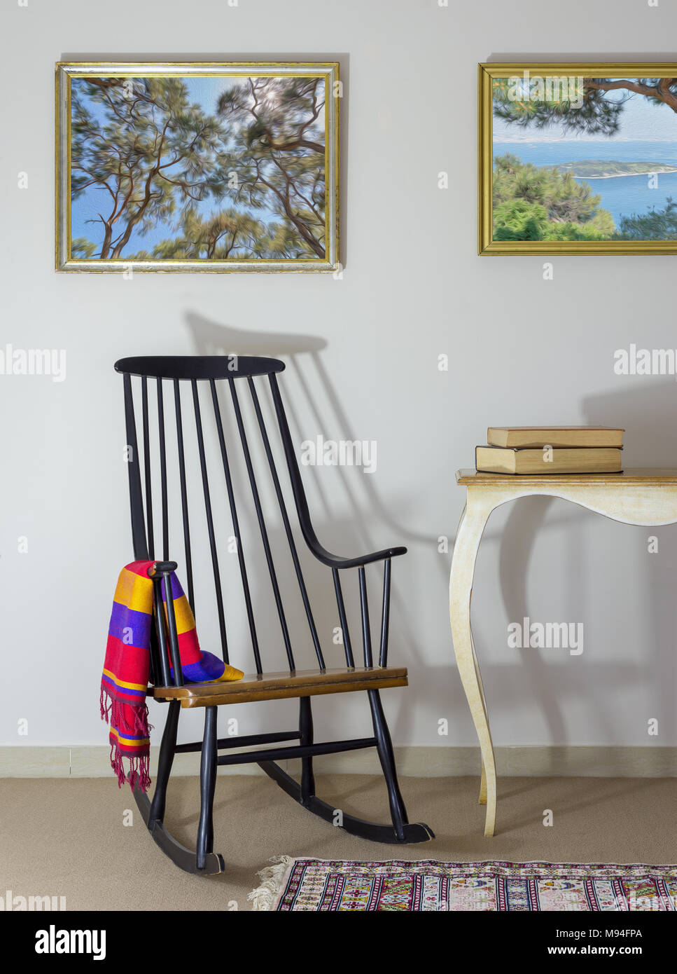 Interior Shot Of Classic Rocking Chair And Two Old Books On Old Style  Vintage Table On Background Of Off White Wall With Two Hanged Paintings  Includin