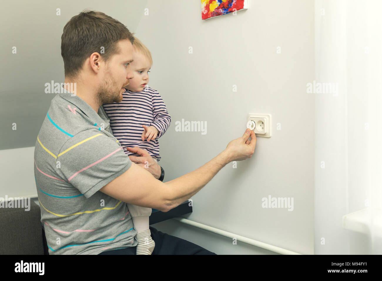 Child Safety At Home Father Takes Care To Protect Kid From Electrical Injury Stock Photo Alamy