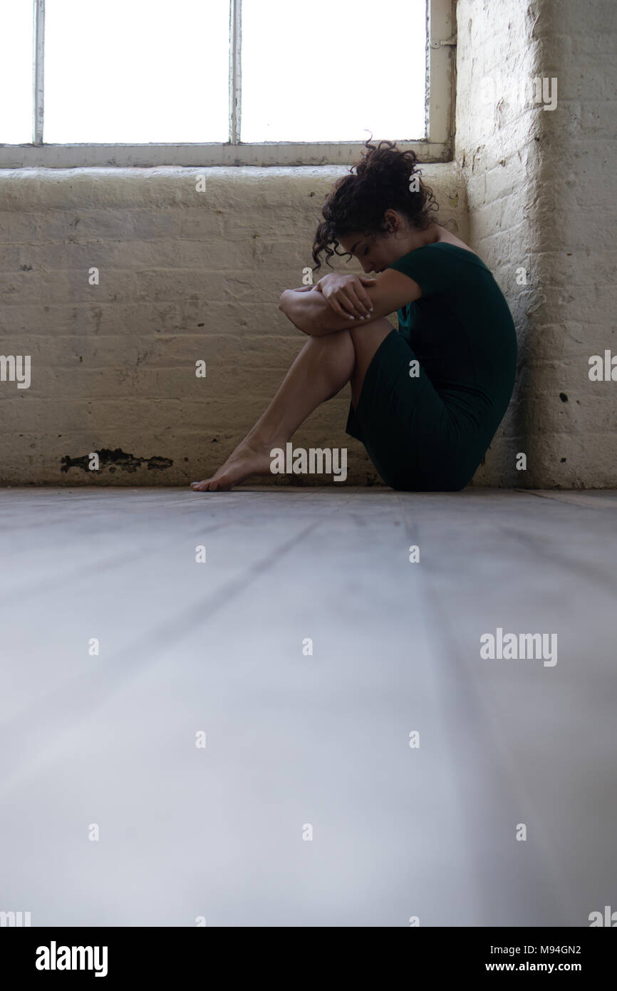 Side view of a sad young woman wearing a dress sat on the floor by the window - Stock Image