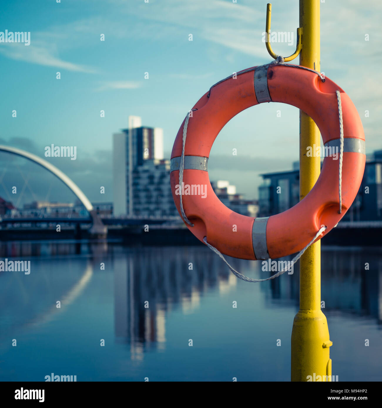 Orange Life Buoy With River Clyde and Arc Bridge in the Background - Stock Image
