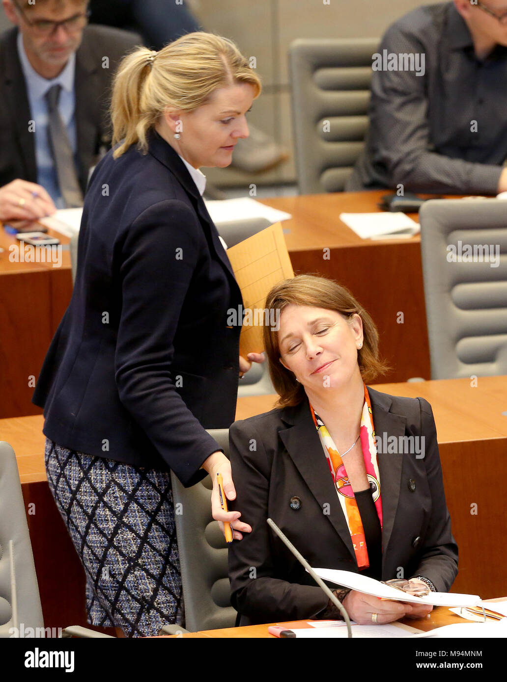22 March 2018, Germany, Duesseldorf: North Rhine Westphalia's (NRW) Minister for Schools, Yvonne Gebauer, of the Free Democratic Party (FDP) being greeted by NRW's Minister for Agriculture of the Christian Democratic Union (CDU), Christina Schulze Foecking, at the session of the north rhine-westphalian state parliament. Topics of the session are rules for the state's art foundation and the introduction of a legislation amendment in schools for nine years of school until A-levels. Photo: Roland Weihrauch/dpa - Stock Image