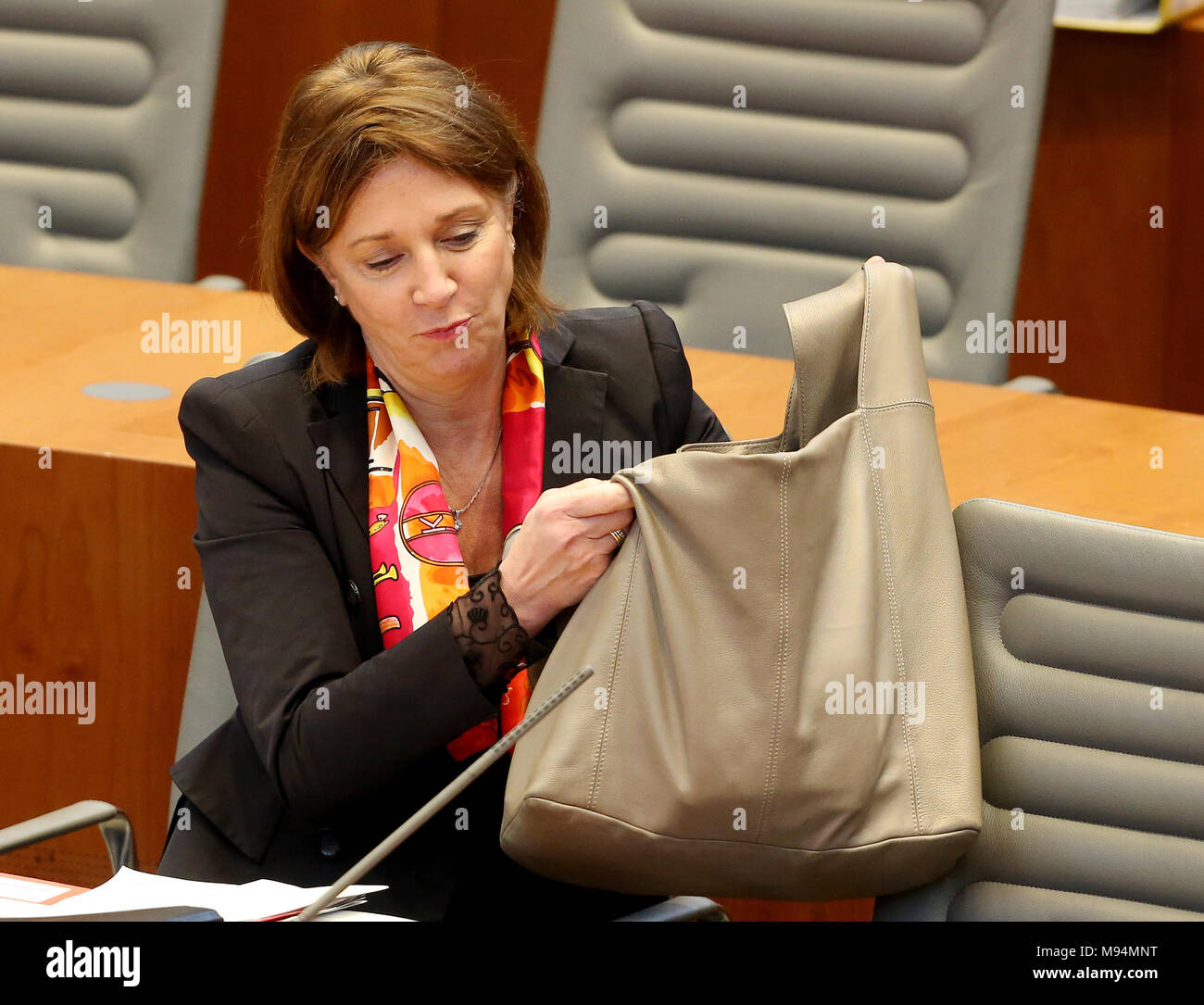 22 March 2018, Germany, Duesseldorf: North Rhine Westphalia's (NRW) Minister for Schools, Yvonne Gebauer, of the Free Democratic Party (FDP) picking up her bag during the session of the north rhine-westphalian state parliament. Topics of the session are rules for the state's art foundation and the introduction of a legislation amendment in schools for nine years of school until A-levels. Photo: Roland Weihrauch/dpa - Stock Image