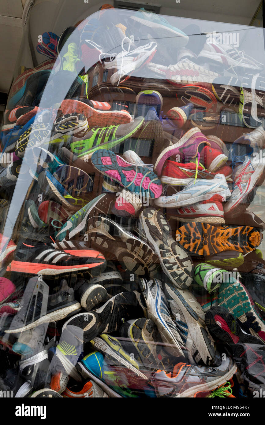 e618316a327f A detail of old trainers are stacked in the window of a sports accessories  shop