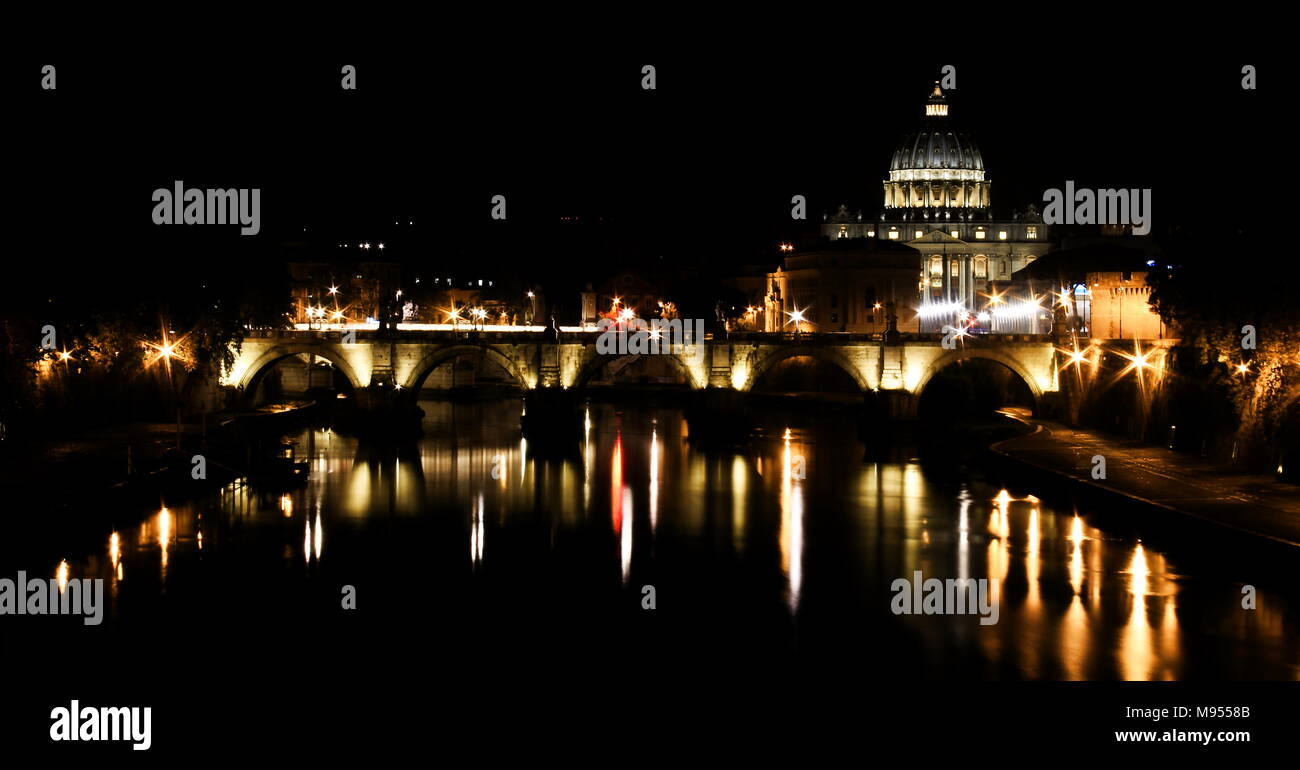 This photo shows a glimpse of the Lungotevere at night. You can see the Sant'angelo bridge, reflected on the water, and the Basilica of St Peter - Stock Image