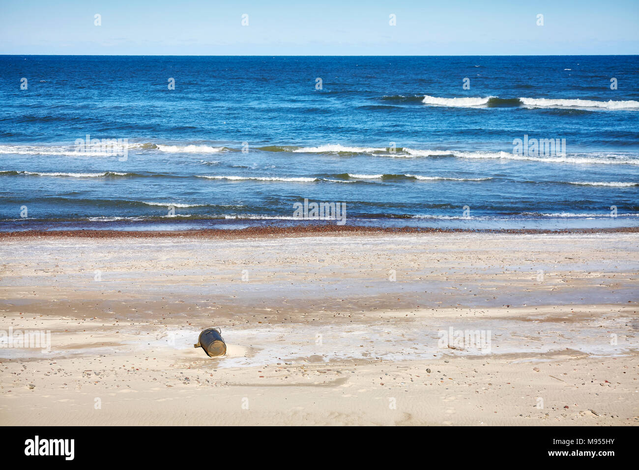 Empty beach with discarded trash can, environmental pollution concept picture. - Stock Image