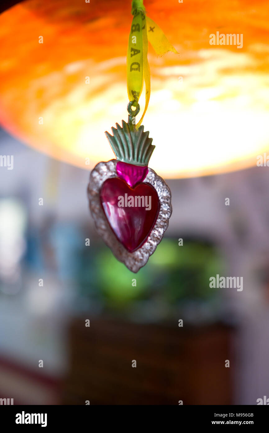 a macro shot of a Mexican sacred heart tin ornament hanging by a yellow ribbon from a chandelier - Stock Image