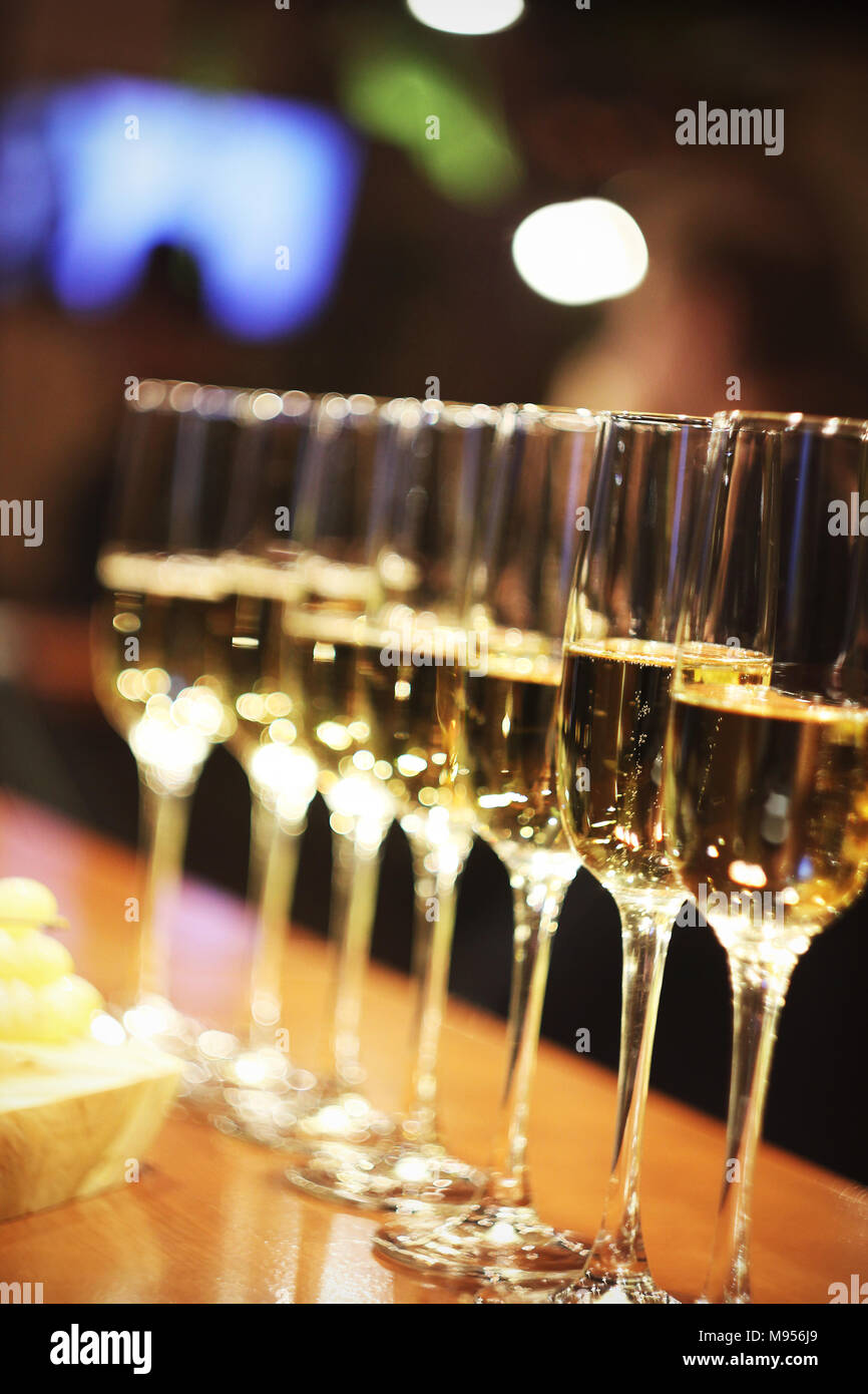 Sparkling wine glasses champagne stand in row at the bar, catering - Stock Image