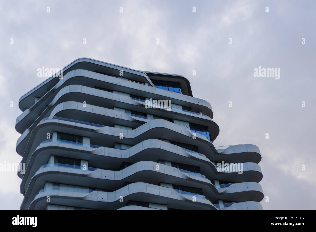 Upper part of Marco Polo Tower at daylight with blue tint. - Stock Image