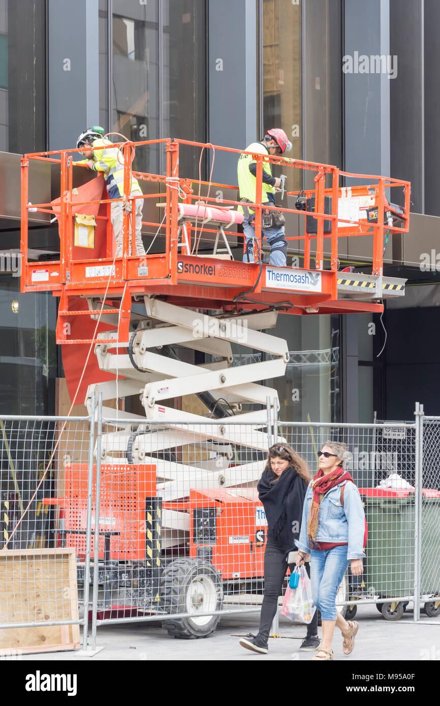 Workmen working on Hydraulic scissor lift on building site, Tuam Street, Christchurch Central, Christchurch, Canterbury, New Zealand - Stock Image