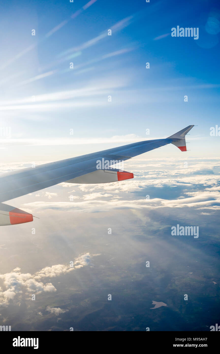 View from an airplane window in mid flight to the airplane wing with blue sky and stratocumulus clouds visible - Stock Image