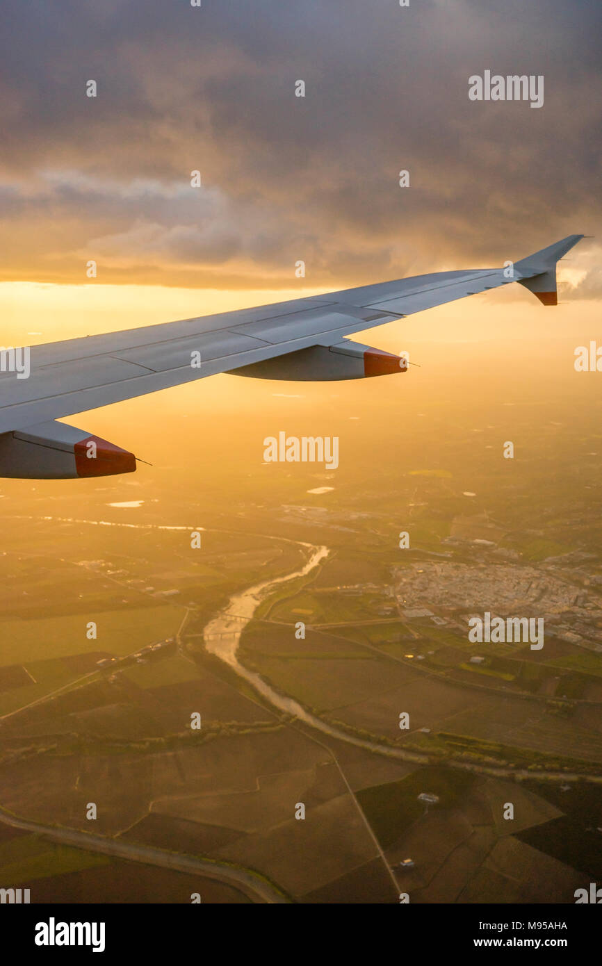 View from an airplane window during landing to the airplane wing with aerial view of the Andalusian landscape in Spain during evening sunset Stock Photo