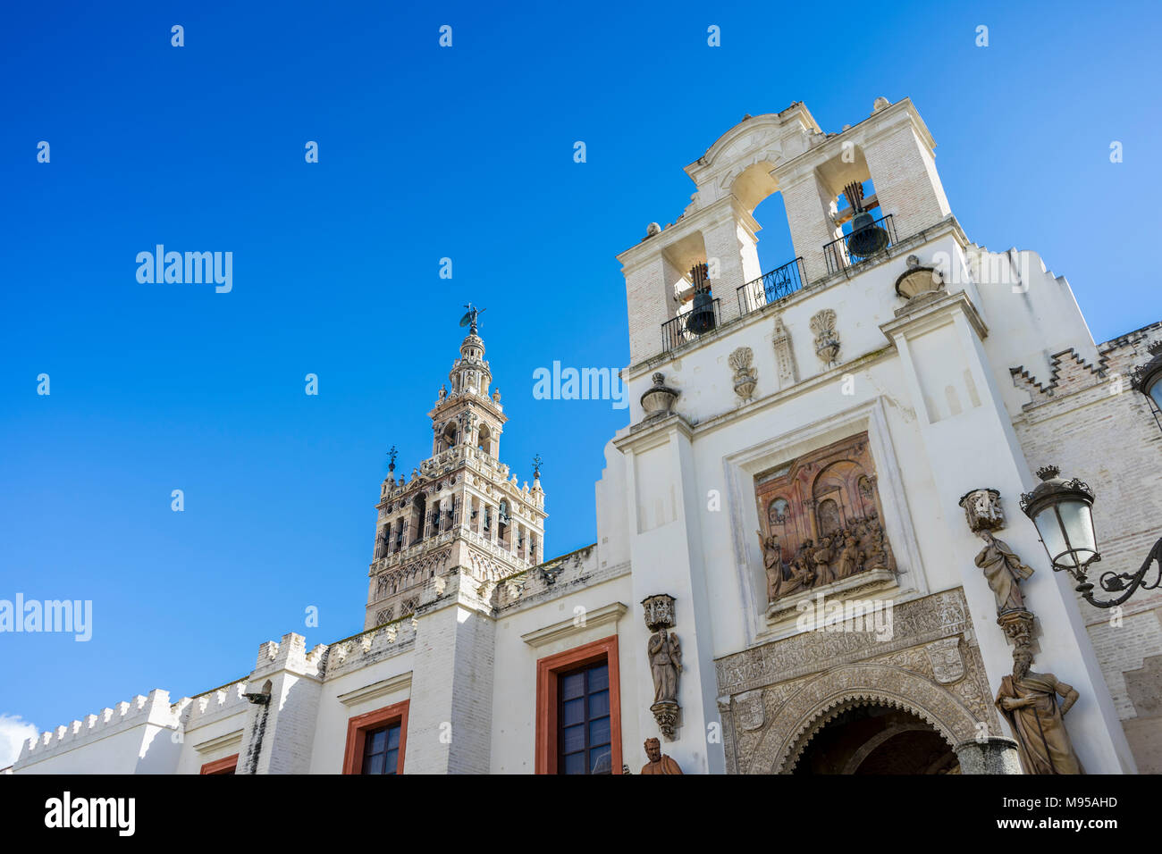 Door of Forgiveness (Puerta del Perdón) with the Giralda clock tower of Seville Cathedral in the background taken in 2018 in Seville, Andalusia, Spain - Stock Image